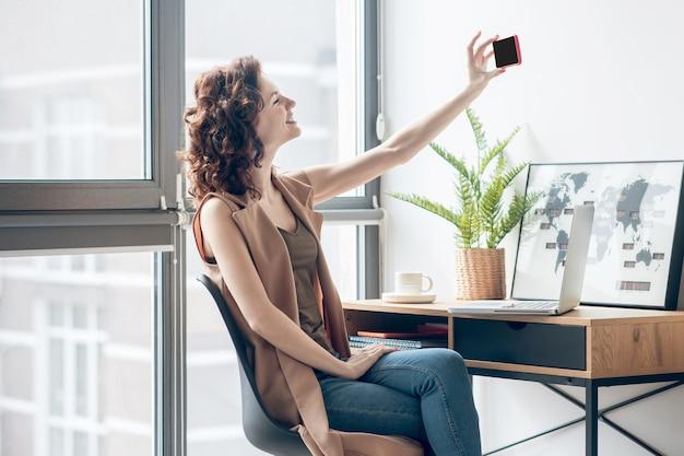 Selfie. mulher jovem sentada perto da janela e fazendo selfie