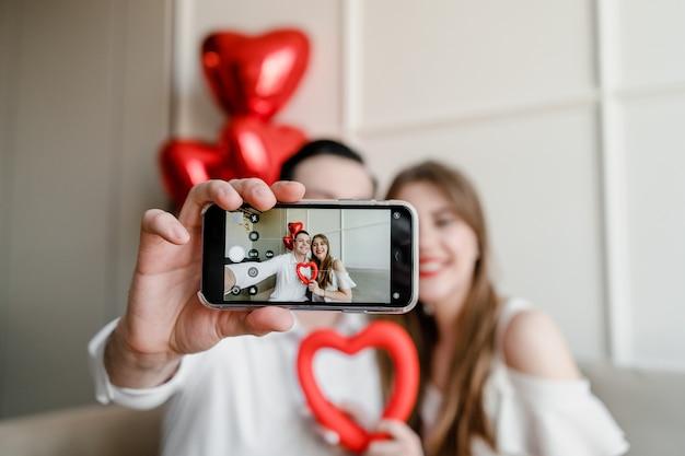 Selfie na tela do telefone do casal bonito em casa no sofá com o coração