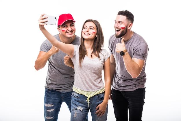 Selfie no telefone do fã de futebol da polônia em jogo de apoio das seleções nacionais da polônia em fundo branco. conceito de fãs de futebol.