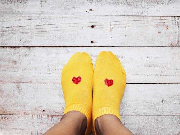 Selfie pés vestindo meias amarelas com forma de coração vermelho na madeira