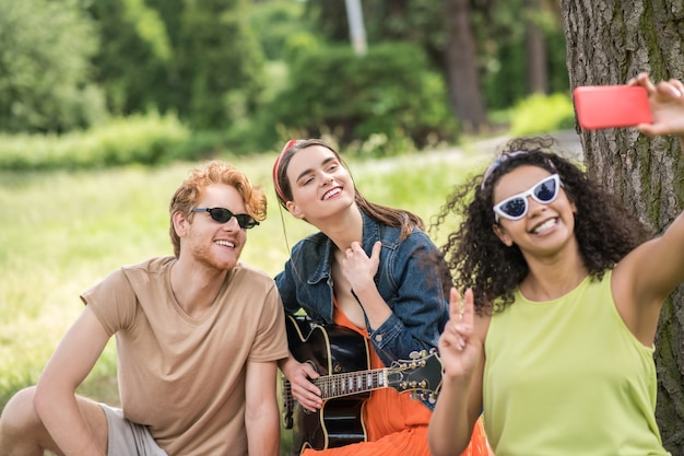 Selfie, piquenique. amigos relaxados alegres em óculos de sol com guitarra tirando selfie no smartphone em um piquenique em um dia ensolarado