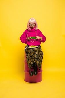 Selfie primeiro, comendo depois. precisa atirar em um prato antes. retrato de mulher caucasiana em amarelo