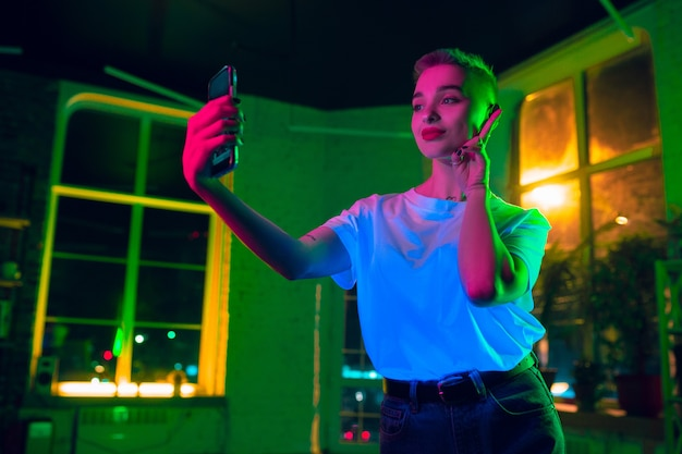 Selfie. retrato cinematográfico de mulher elegante no interior iluminado por néon. tons de efeitos de cinema, cores neon brilhantes. modelo caucasiano usando smartphone em luzes coloridas dentro de casa. cultura jovem.