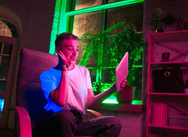 Selfie. retrato cinematográfico de mulher elegante no interior iluminado por néon. tons de efeitos de cinema, cores neon brilhantes. modelo caucasiano usando tablet em luzes coloridas dentro de casa. cultura jovem.