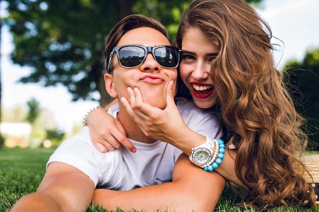 Selfie-retrato de casal engraçado deitado na grama em um parque de verão. garota com cabelo longo cacheado, lábios vermelhos e cara jovem em óculos de sol imitando a câmera.