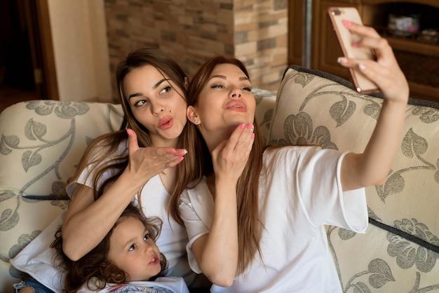 Selfie retrato de duas raparigas e uma menina no sofá em casa.