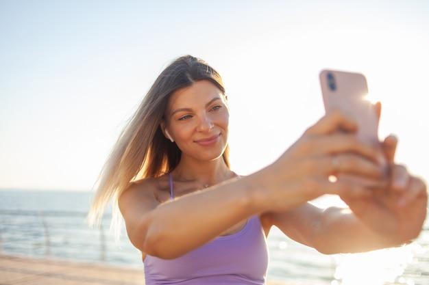 Selfie retrato de uma jovem loira, vestida com roupas esportivas na praia ao nascer do sol
