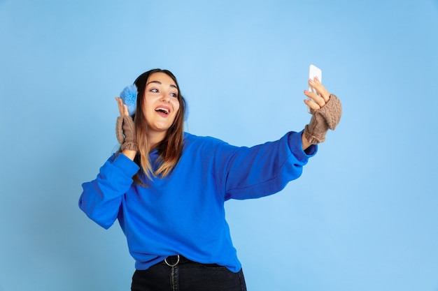Selfie. retrato de uma mulher caucasiana sobre fundo azul do estúdio. linda modelo feminino com roupas quentes. conceito de emoções humanas, expressão facial, vendas, anúncio. clima de inverno, época de natal, feriados.