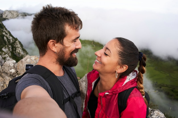 Selfie sorridente, jovem casal na montanha.