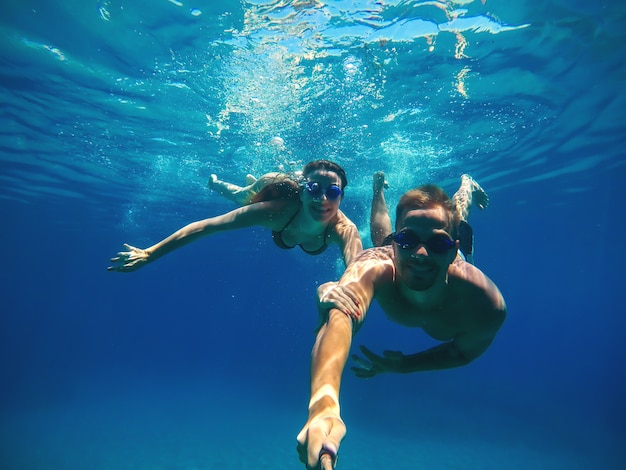Selfie subaquático com um pedaço de pau de um casal de amor bonito feliz nadando no mar turquesa sob a superfície para as férias de verão.