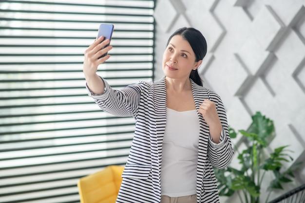 Selfies. bela morena adulta em pé com um smartphone na mão estendida, olhando para o levantamento de tela.