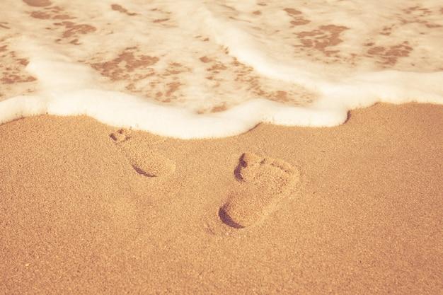 Selo de pés em areia na praia com sol na parte da manhã, estilo de cor vintage
