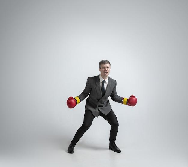 Selvagem e jovem. homem caucasiano com roupa de escritório de boxe com duas luvas vermelhas na parede cinza. treinamento de empresário em movimento, ação. olhar incomum para esportista, atividade. esporte, estilo de vida saudável.