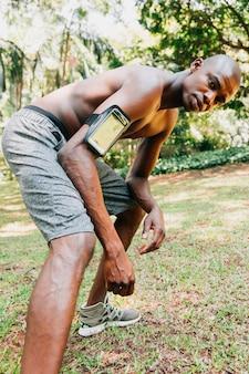 Sem camisa cabe jovem com telefone celular no caso de braçadeira, esticando a perna
