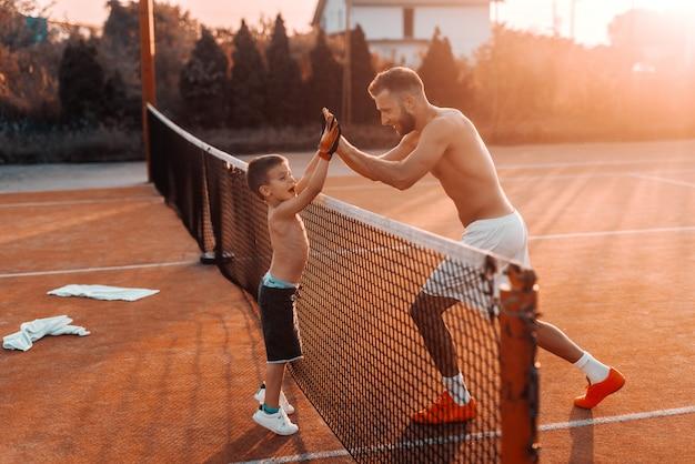 Sem camisa feliz pai e filho dando cinco uns aos outros sobre a rede de tênis. manhã no verão.