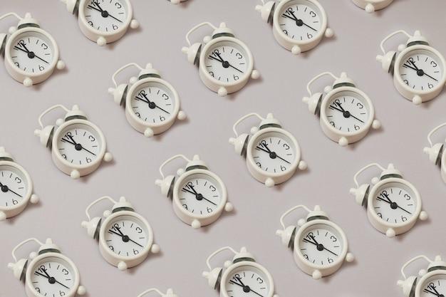 Sem costura padrão moderno feito de despertador retrô branco, mostrando de cinco minutos a meio-dia em fundo de papel cinza com espaço de cópia. postura plana. espaço negativo.