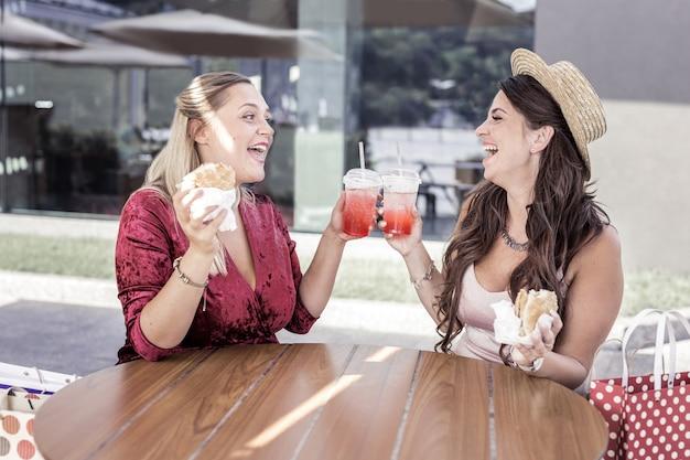 Sem dieta. mulheres agradáveis e felizes sorrindo umas para as outras enquanto desfrutam de sua refeição pouco saudável