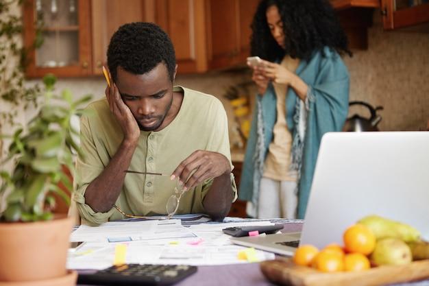 Sem dinheiro família jovem com problemas financeiros. homem africano frustrado com óculos e lápis nas mãos, olhando papéis na mesa com uma expressão estressada e intrigada, pagando contas online em casa