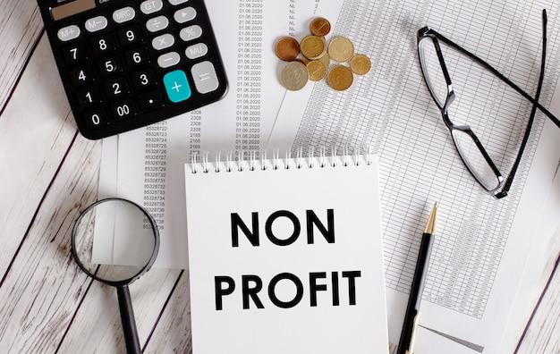 Sem lucro escrito em um bloco de notas branco perto de uma calculadora, dinheiro, óculos, uma lupa e uma caneta