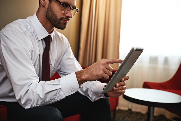 Sem tempo para descansar. foto recortada de homem de negócios com mala e tablet sentado no sofá na entrada do hotel