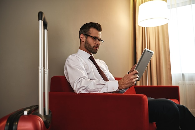 Sem tempo para descansar. homem de negócios de óculos com mala e tablet sentado no sofá na entrada do hotel