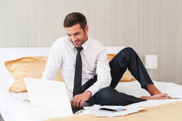 Sem tempo para descansar. jovem bonito de camisa e gravata trabalhando no laptop e sorrindo enquanto está sentado na cama no quarto do hotel