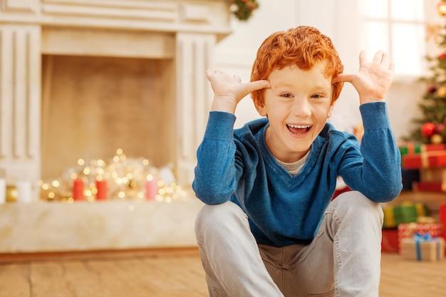 Sem tempo para preocupações. criança extremamente feliz ficando animada e sorrindo enquanto faz caretas engraçadas em casa.