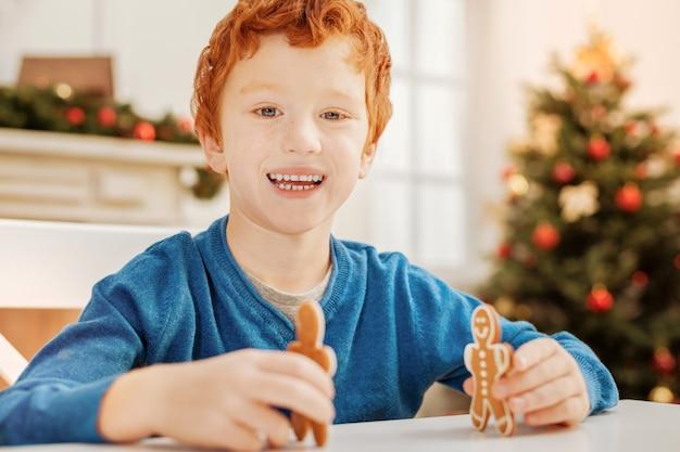 Sem tempo para preocupações. garoto ruivo emocional sorrindo enquanto se diverte e brinca com os bonecos de gengibre em casa.