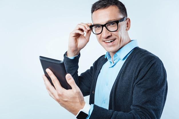 Sem tempo para preocupações. homem educado vestindo um traje casual elegante, tocando seus óculos enquanto olha para a câmera com um largo sorriso no rosto com um tablet digital na mão.