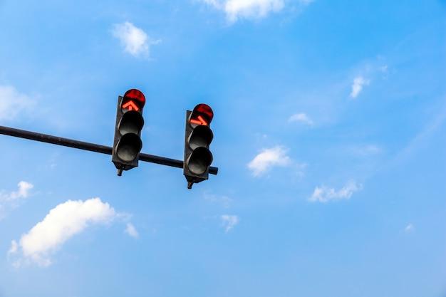 Semáforo com cor vermelha no fundo do céu azul