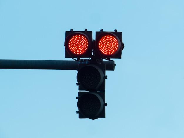 Semáforo com luz vermelha acesa, com céu azul.