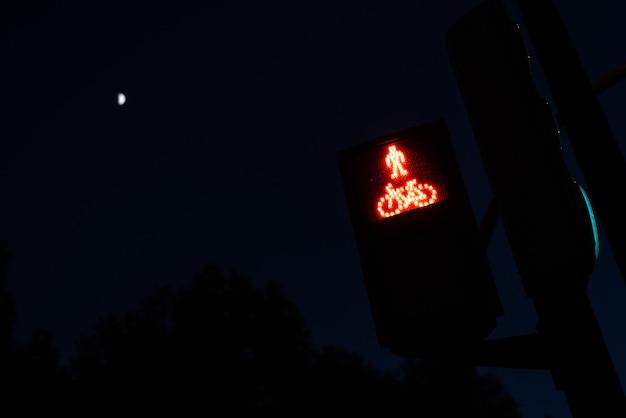 Semáforo com luzes vermelhas para pedestres e ciclistas, com figura de um ciclista.