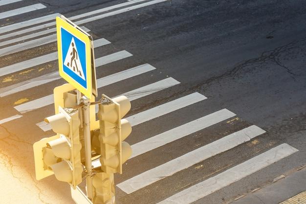 Semáforos ao longo do cruzamento urbano. um semáforo com uma placa de travessia de pedestres ilumina-se na cidade, sob o sol poente