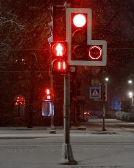 Semáforos com vermelho para transporte e pedestres durante uma queda de neve durante a noite. sinal de parada.