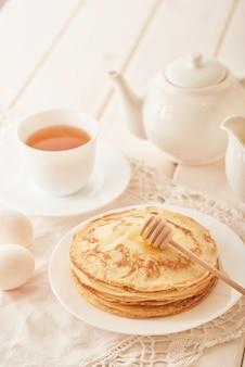 Semana da panqueca: panquecas com mel e chá na mesa
