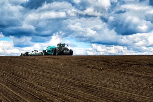 Semeando o trabalho no campo na primavera. trator com semeadora.