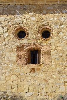 Semelhança de rosto em fachada de casa de pedra antiga, olhos e boca. pedraza, espanha.