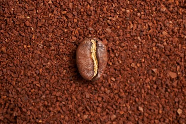 Semente de café no fundo de café moído.