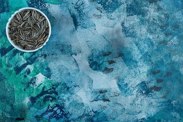Semente de girassol orgânica em uma tigela na superfície azul