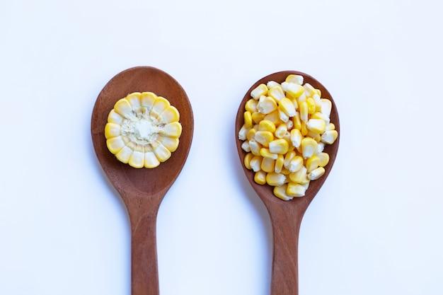 Semente de milho cru na colher de madeira no fundo branco