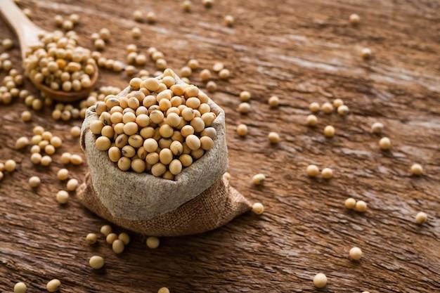 Semente de soja em saco de saco de cânhamo com fundo de madeira. nutrição vegetal alimentos crus orgânicos oi proteína. alimento para o conceito de boa saúde.