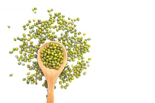 Semente fresca crua dos feijões de mung ou feijões verdes orgânicos em uma colher de madeira.