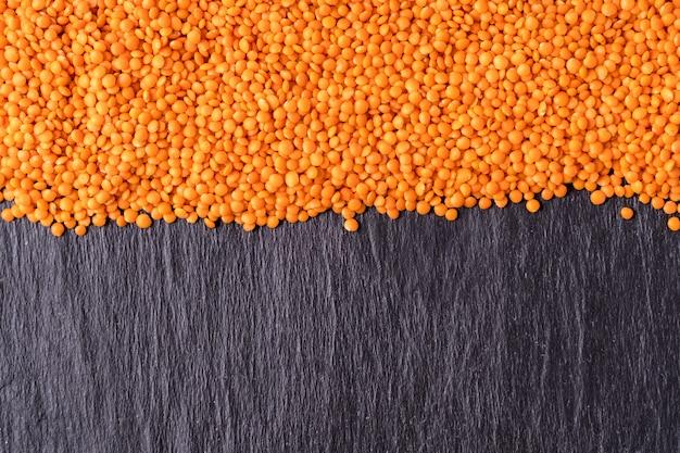 Sementes alaranjadas pequenas das lentilhas da planta anual da leguminosa.
