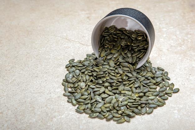 Sementes de abóbora. as sementes de abóbora descascadas estão em um pires preto. em uma tábua de corte preta feita de pedra.