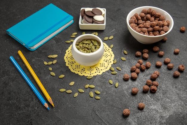 Sementes de abóbora frescas de vista frontal com flocos de chocolate e biscoitos no fundo cinza.
