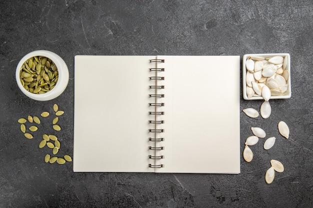 Sementes de abóbora frescas de vista superior com o bloco de notas na foto escura de sementes de frutas maduras