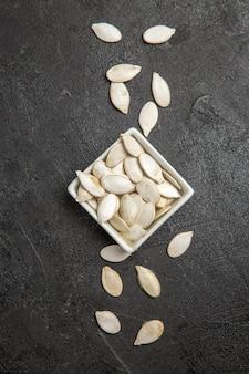 Sementes de abóbora frescas de vista superior na foto escura do grânulo de semente de fundo