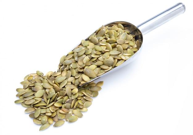 Sementes de abóbora (sementes descascadas) em pá de metal (coleção de várias nozes). isolado