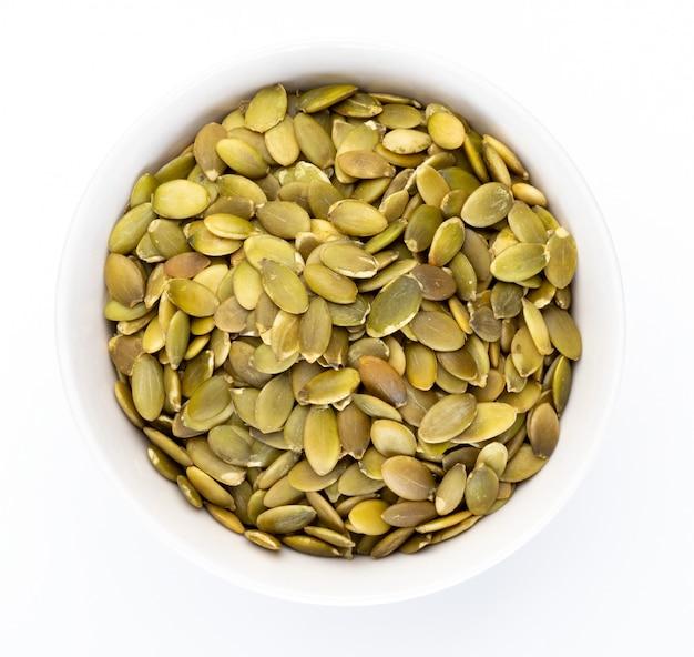 Sementes de abóbora (sementes descascadas) em tigela branca (coleção de nozes diversas). isolado