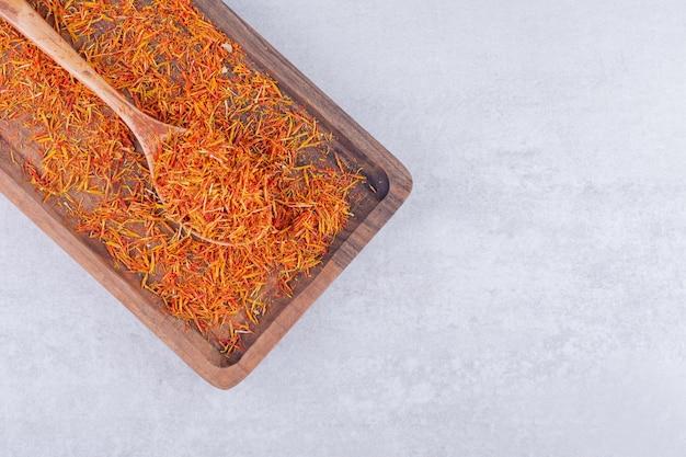 Sementes de açafrão em uma bandeja de madeira com fundo de concreto. foto de alta qualidade